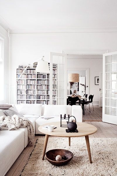 Homes danish the living room with a coffee table and bookshelves in the background bookshelves throws a muted rug and the hans wegner coffee table