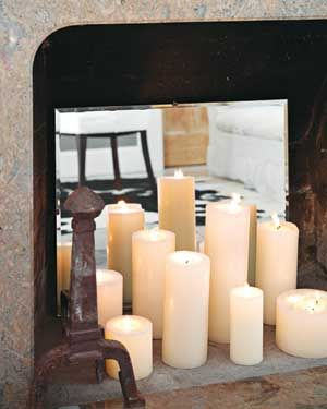 candles in fireplace with mirror in it to reflect back and make there seem like more