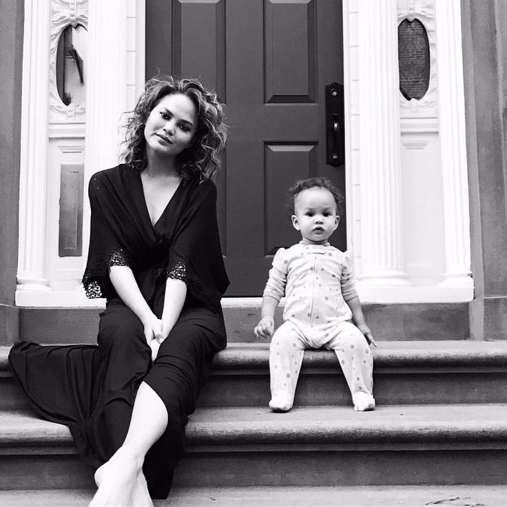 Chrissy Teigan sitting infront of a front door with baby Luna