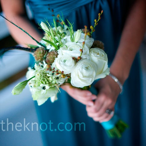 White ranunculus, scabiosa and garden roses were tied together into loose natural arrangements, with a few small feathers mixed in.