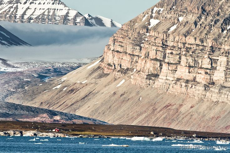 A cabin on the shores of the Kongsfjord in Svalbard is towered over by mountains and glaciers