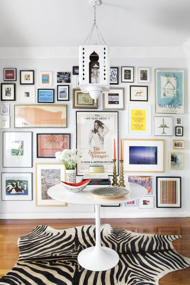 Eclectic living space with a large gallery wall and  faux zebra rug