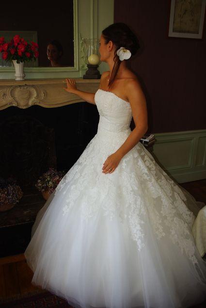 Robe de mariée couleur ivoire, de créateur espagnol White One. Robe bustier en dentelle, réhausser d'un ruban en satin et de perles sous poitrine.
