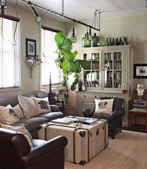 Trunk coffee table, but also piping at ceiling for lights!  Love the conduit stuff, the bottles on top of the bookshelf, the eclectic feel of this photo.