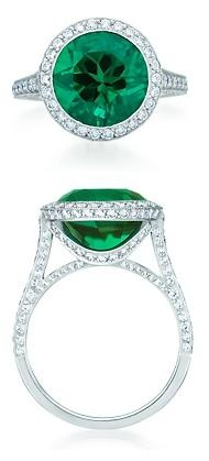 Tiffany and Co ring in platinum with a round brilliant emerald haloed by round brilliant diamonds. Emerald, carat weight 4.82; diamonds, carat total weight .79.