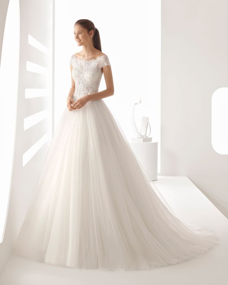 Princess-style beaded lace and tulle wedding dress with bateau neckline, sheer inserts and full skirt. 2018 Rosa Clará Collection.