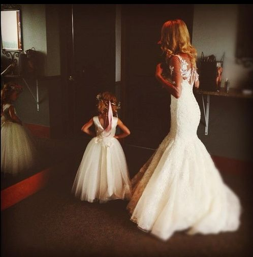 I think this is adorable. The flower girl and bride looking in the mirror together. or looking at each other..thast might be cute