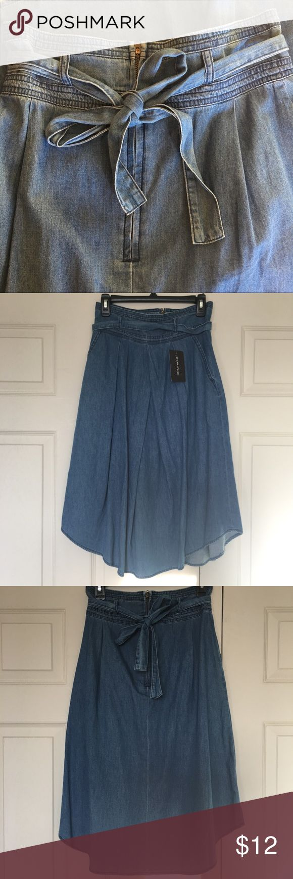 Jean Skirt NWT Jean material skirt with zipper in the back and tie around waist.  Tie can be removed if not wanted to be used.  Has pockets on sides.  Past knee length   Purchased in boutique store.   Waist 14in/36m side to side Length from waste to gem 30in/76m Size 6 Promod Skirts