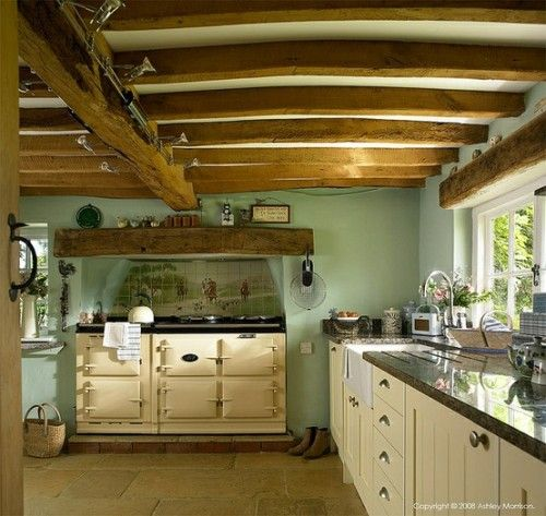 Gorgeous wood beams line the ceiling of this English country kitchen. Lovely sage green complements the warm woods.