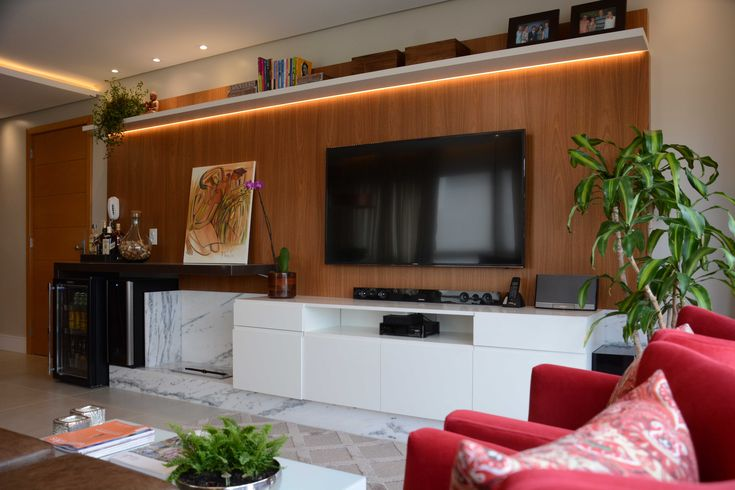ESTAR INTEGRADO com jantar e cozinha, com móveis e acabamentos em alto padrão. O painel madeirado foi usado tanto para a TV e equipamentos, quanto para a criação de um espaço de bar, com adega e cervejeira. Aliando os elementos, lareira ecológica em base de mármore branco.