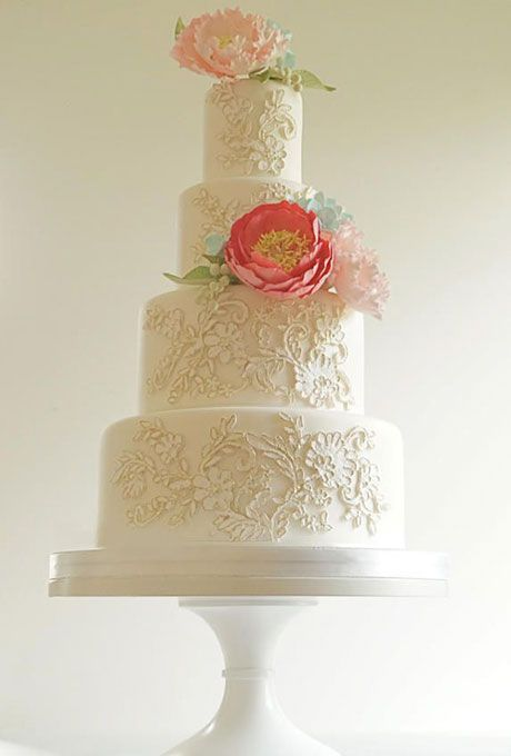 Four-Tier Lace Wedding Cake with Pink and Coral Sugar Flowers. Gold-edged lace appliques add another layer of dimension to this design by Steel Penny Cakes. Pink and coral sugar peonies, blue hydrangeas, and green berries are the perfect finishing touch.