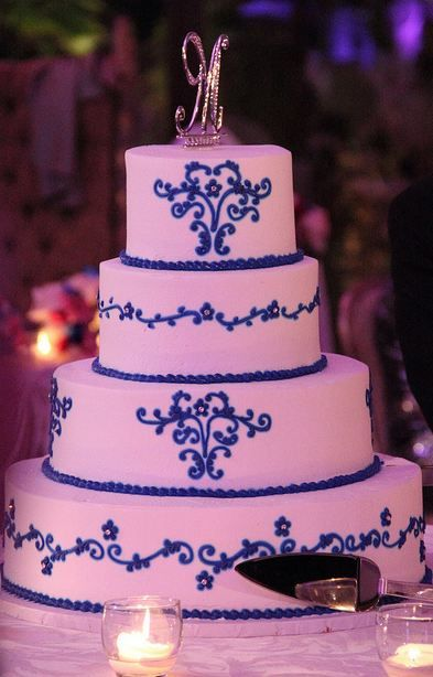 Four tier white round wedding cake with blue trim and crystal monogram topper.JPG