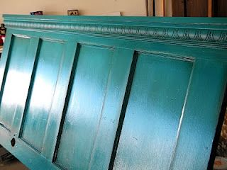 Old door with crown molding around the top as headboard.