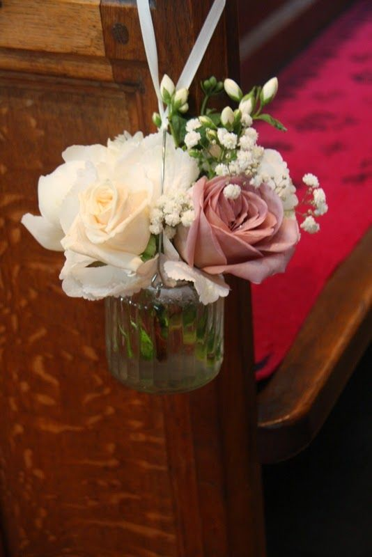 "the pews were decorated with Jam jars filled with posies of Vendella & Amnesia Roses, ""Bowl of cream"" Peonies, Philadelphus Snowbelle and Gypsophilia"
