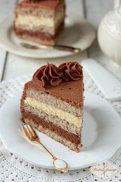 Pyszny tort czekoladowo-orzechowy. Biszkopt na bazie orzechów laskowych przekładany dwoma kremami: z czekolady białej i z czekolady mlecznej.