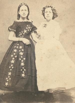 "1860s fancy dress - the girl on the left may be ""starry night"" and the girl on the right ""spring"" or ""flora"" or something along those lines."