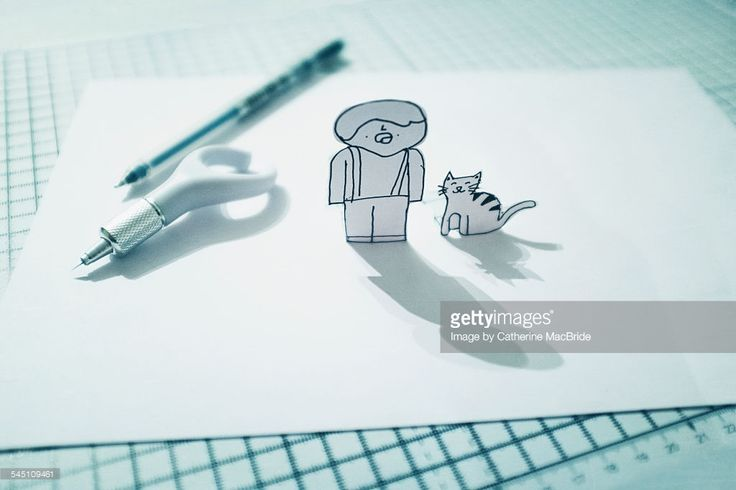 Two cartoon characters drawn in pen and cut out of the sheet of paper so they stand upright.