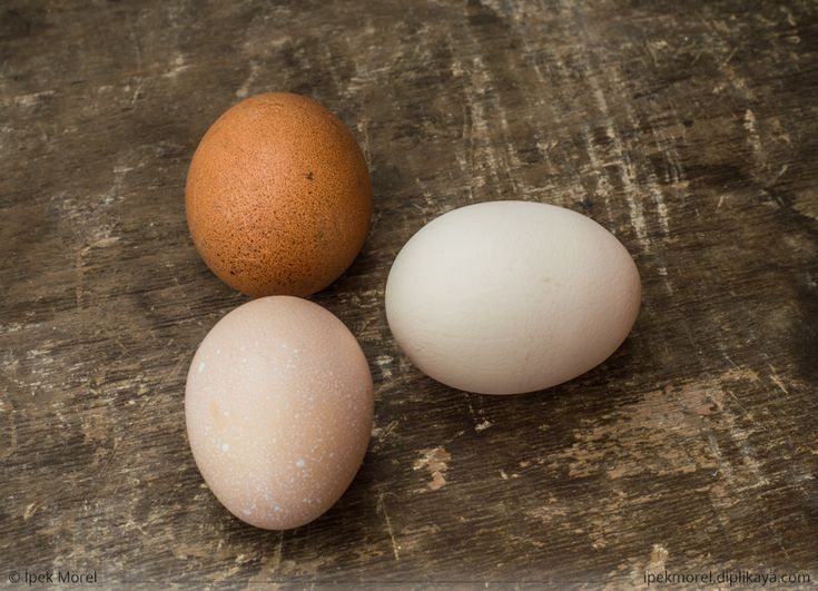 Three fresh chicken eggs on an old wooden table
