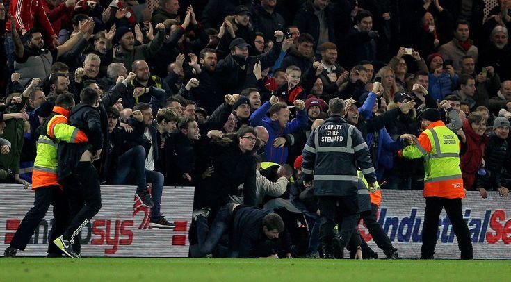 Liverpool fanúšikovia rozliať na ihrisku po tom, čo Liverpool Adam Lallana strelil tretí gól po boku svojej