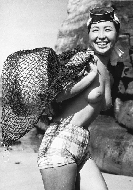 """A Japanese skin diver or """"Ama"""" near the small fishing village of Onjuku in the Chiba prefecture of Japan, August 1959. Divers reach depths of nearly 15 metres to collect seaweed, which they transfer to wooden tubs floating on the surface. The weed is eaten locally as well as being exported for use as a food additive. (Photo by Keystone Features)"""