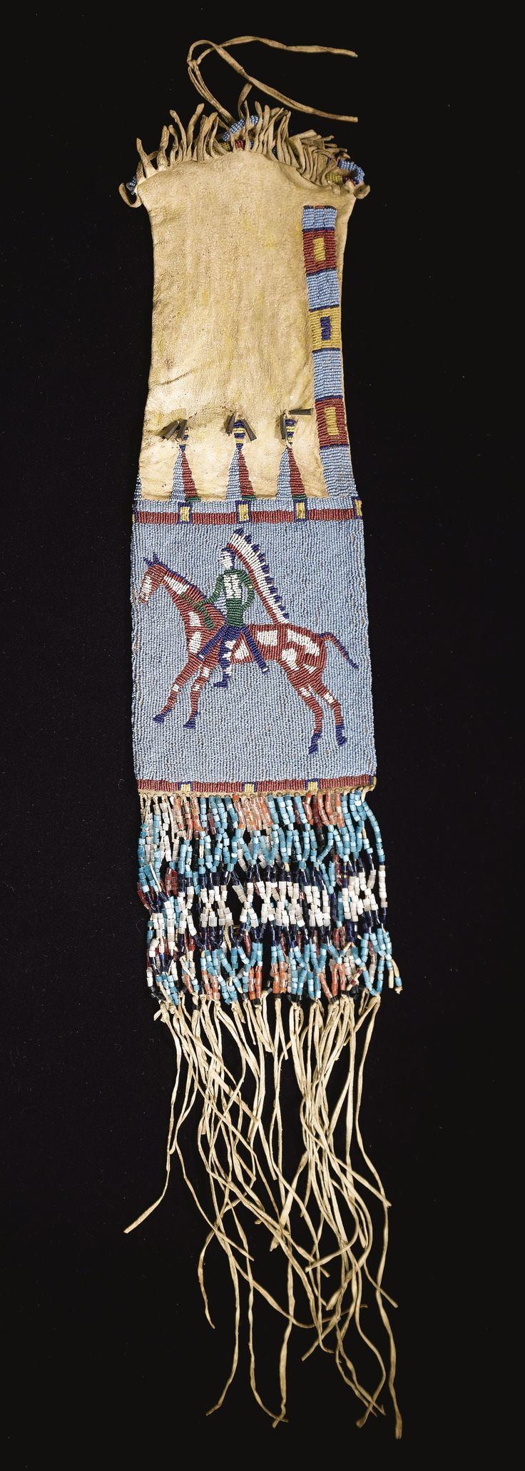 SIOUX PICTORIAL BEADED AND FRINGED HIDE TOBACCO BAG    composed of finely tanned hide decorated with yellow ochre, finely sinew-sewn in numerous colors of glass beadwork against a light blue ground, with equestrian figures on both sides, each wearing a traditional costume and feather bonnet, the broad beaded panels surmounted by triangles spot-stitched on the hide ground, trimmed with tin cone pendants, the lower section decorated with fringe, profusely strung with tu