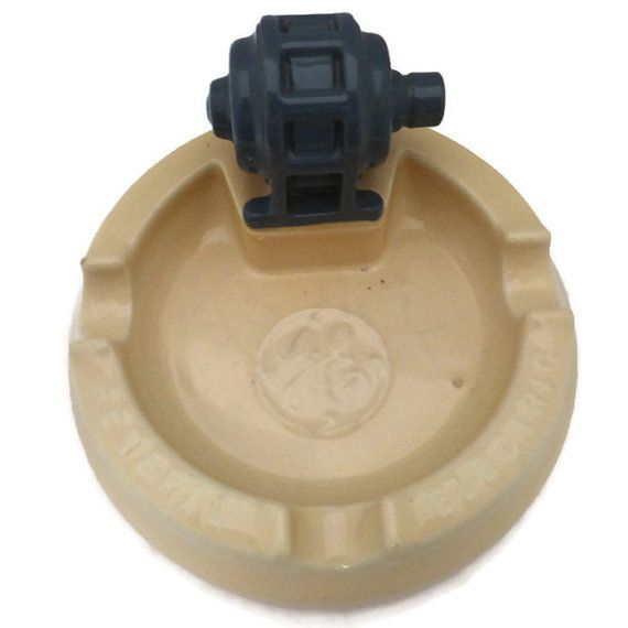 This is a vintage motor General Motors ashtray was probably a dealer promotional item advertising GE motors This cool piece of pottery depicts a motor