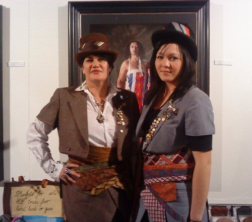 """Artist and designer Suzanne Tamaki and her daughter were head to toe in Tamaki's designs, including her silk tie belt-wraps and quasi-Victorian jackets and top hats. In the background, """"Blankets for sale – WE trade for land, beads, or guns"""" is embroidered on wool, stabbing at colonial land-grabbing via the needle."""