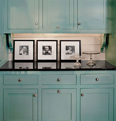 Peacock blue painted cabinets with black countertop and white backsplash.