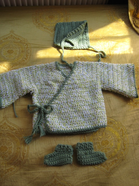 This is my version of the baby kimono from my crochet board.  I crocheted the sleeves directly onto the body. Then I'd join each round with a sl st, ch1, turn. They tapered by increasing by 1 sc at the end of each round.  I also chose not to put the inside tie as I think it would be tricky for mom to tie with a squirmy baby and that it would be more comfy for baby. I added a bonnet and booties to complete the set.