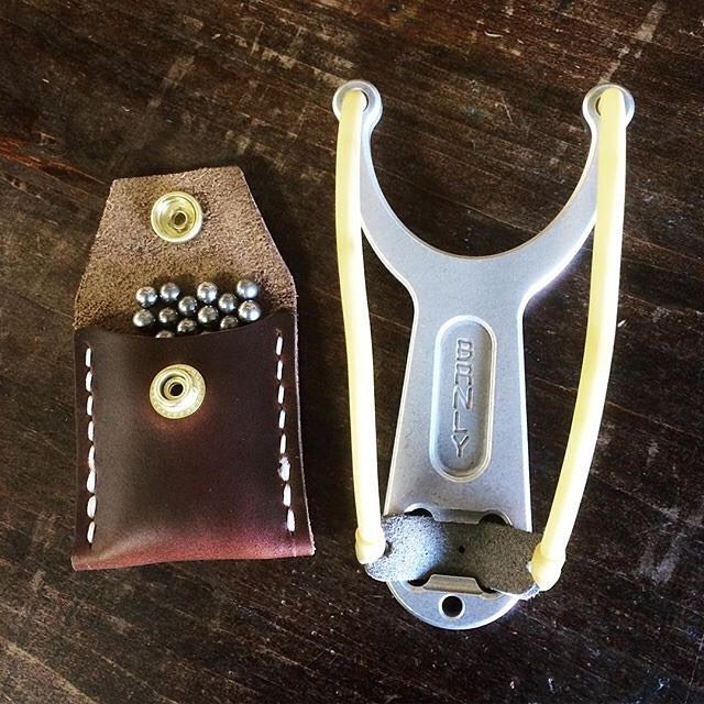 A tactical slingshot captures the imagination big time - the simplicity of one of early man's first tools of leverage over his world is virtually unchanged - except for the titanium and surgical rubber parts and steel bearing projectiles! Here's a combination the leather pouch by @fiends and the slingshot from @burnleyknives! Tell ' em EDC Armory sent you! #slingbow #post