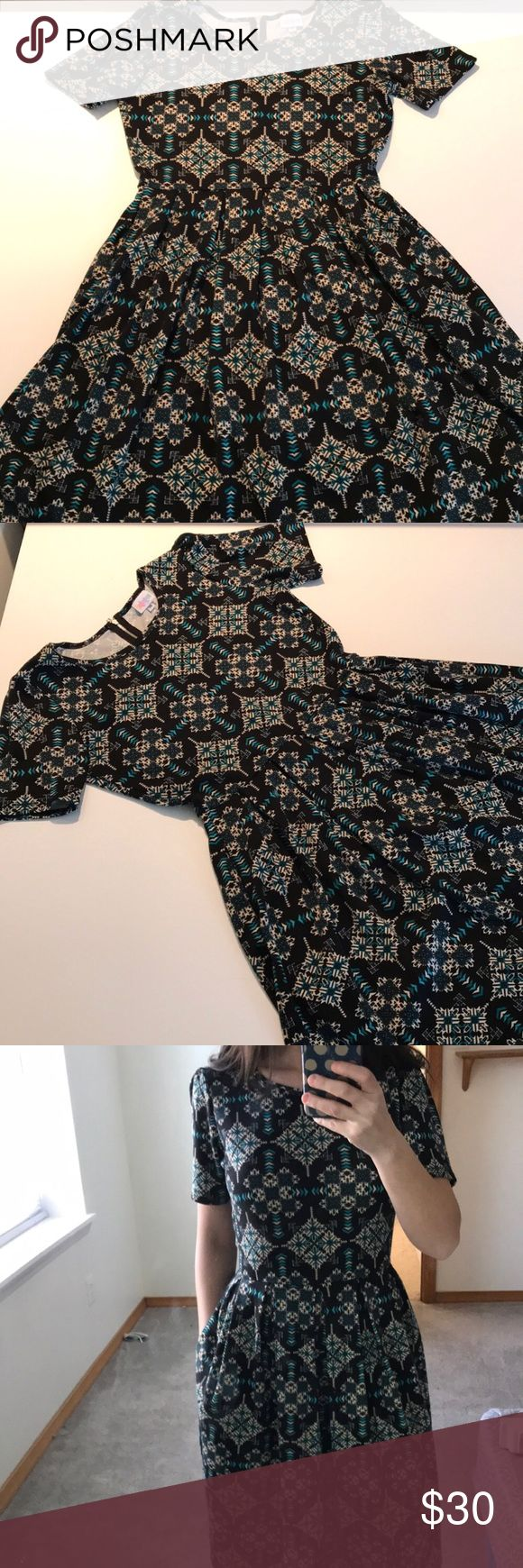 LulaRoe Amelia The Amelia Dress' stretchy knit fabric is comfortable enough to let you wear the dress all day, while having the structure and tailoring that make it sophisticated enough for the office or a fancy night out. Looks great on all body types. Black background with turquoise and off white Aztec pattern pairs great with a denim or leather jacket! This is a pre-owned, pre-worn dress, so there are normal signs of wash and wear, (ie: some fading and some piling). Price reflects…