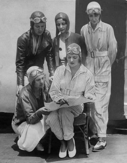 Famous women pilots preparing to take part in the 1934 Memorial Day air races at Dycer Airport. In front row kneeling is Gladys O'Donnell, who last year entered seven races and won six. Seated is Ruth Elder, famous flying beauty. Standing left to right: Kay Van Doozer, Myrtle D. Mims and Clema Granger.