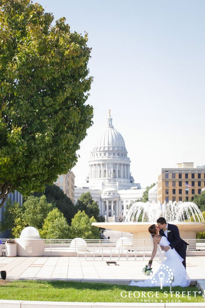 This bride and groom celebrate their big wedding day on the rooftop at Monona Terrace, with Madison's beautiful Captiol serving as the perfect backdrop. Photograph taken by George Street Photography.