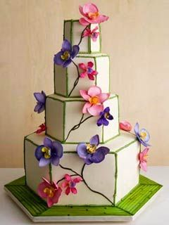 Interesting four tier hexagon wedding cake, decorated with green bamboo trimming in all the corners and pink and purple orchid flowers.