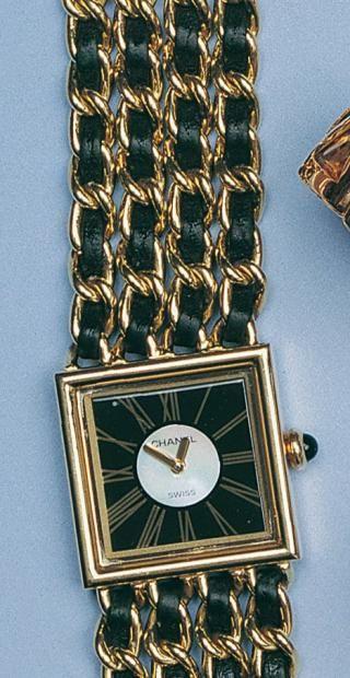 """Beau bracelet montre de marque """"CHANEL"""" modèle """"Mademoiselle"""", en or jaune. La montre est de forme carrée, fond noir, cadran interne nacré blanc, chiffres romains pour les heures, mouvement quartz. Le bracelet est composé de quatre mailles gourmettes, entrelacées de liens en cuir noir. Le remontoir est serti d'un cabochon en onyx."""