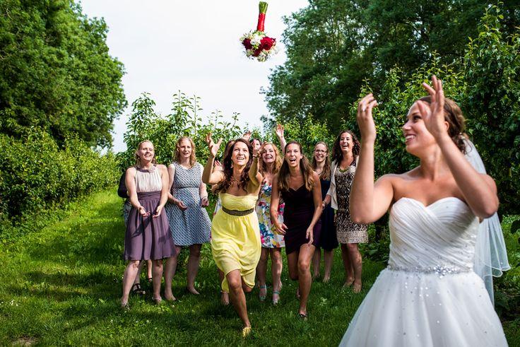 mooi fotomoment de bruid gooit haar boeket weg bruidsreportage de olmenhorst