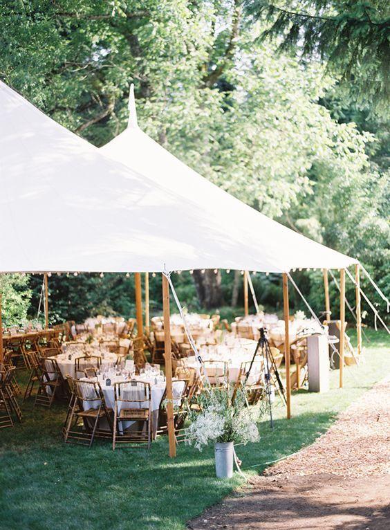 Carpas simples para una boda al aire libre en otoño. Preciosos postes de madera y luces a lo largo de los aleros.