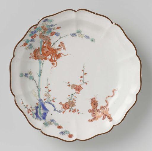 Gelobd bord met draak, tijger, bamboe en prunus, Onbekend. 1670 - 1690,(aannemelijk) China. Porselein.  Ik vind dit geheel met elk detail erg goed staan voor Acient China. De draak heeft te maken met de keizerlijke famillie, en de tijger met de koning (Wang), hierbij kijkt de tijger op naar de draak. Bamboe staat voor Wijsheid en Kracht, waar de prunus (een soort vruchtenboom zoals kersen en pruimen) staat voor langleven en vruchtbaarheid. Ook staat het gouden randje voor welvaard en…
