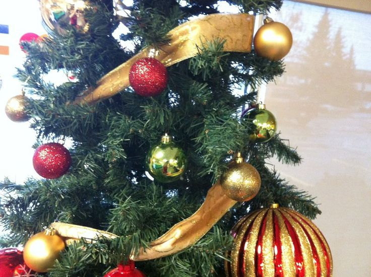 """Gold ribbon wrapped around a Christmas tree is a great way to take a tree from """"pretty"""" to """"WOW""""!"""