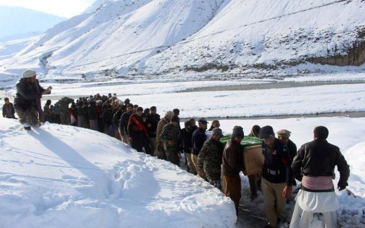 Pakistani volunteers and army soldiers carry a body of a villager killed in an avalanche in Upper Chitral in Pakistan, Monday, Feb. 6, 2017. A Pakistani security official says at least 13 people have been killed in an avalanche that buried five homes following heavy snowfall in the country's north.