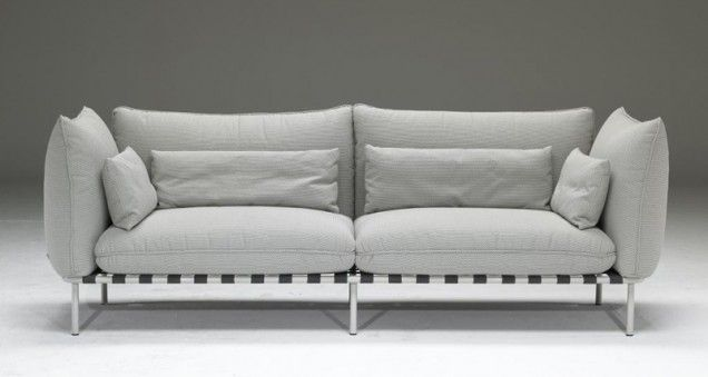 A striking modern sofa suspended above long metal legs, Clubs' visible belts make for both decorative and structural elements that support the seat cushions. Four pillows offer extra comfort.  Dimensions  89 inches width  39 inches depth