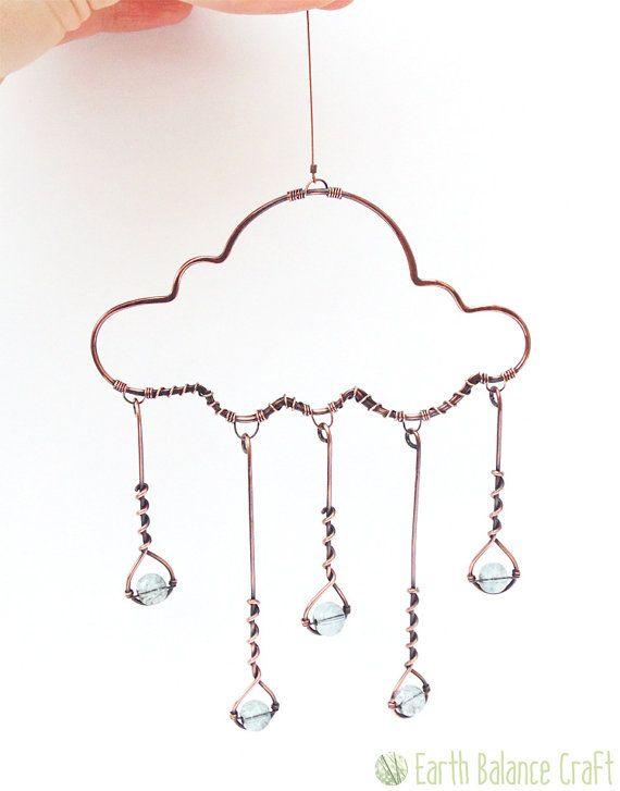 Regen Wolke Suncatcher  Ein poliertes Kupfer Regen Wolke hängende Dekoration mit fünf blaugrau glitzernde Glas Regentropfen fallen auf den Boden unten. Dieses Design ist kinetische mit baumelnden Tröpfchen, die mit Bewegung sanft schwingen. Dieses hübsche Stück Draht Wanddekoration eignet sich zum Aufhängen im Haus als eine funkelnde Fensterdekoration oder heraus in den Garten, wo die Sonnen Strahlen, durch das Glas streamen kann. Eine skurrile Kunst Wandgestaltung, die Teil einer Sammlung…