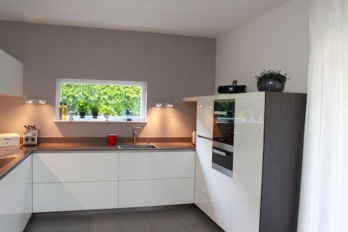 Witte keuken met warme bruintinten in U-vorm. Keukendealer: www.coninxkeukens.nl