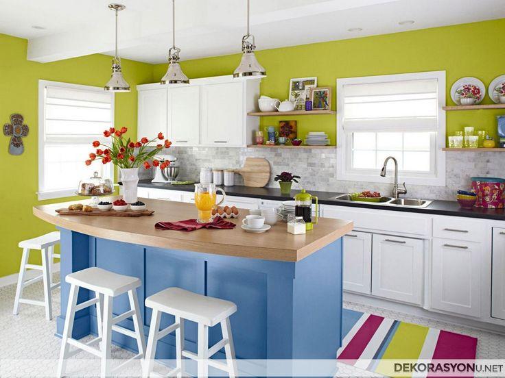 Mutfağınızın cıvıl, cıvıl renklerle spesifik bir tasarıma sahip olmasını istemez misiniz? Yeşil duvar dekorasyonu, siyah tezgahlı beyaz dolapları, mavi ada kısmının tepesinde yer alan ahşap