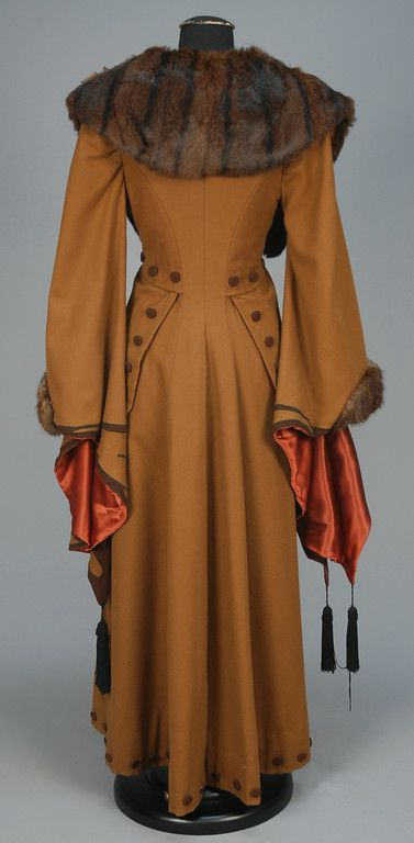 WOOL COAT with APPLIQUE and FUR TRIM, EARLY 20th C. Light brown with exaggerated wizard sleeve appliqued in darker brown with black silk tassels, fur collar and cuff, contrasting faux button trim and satin lining