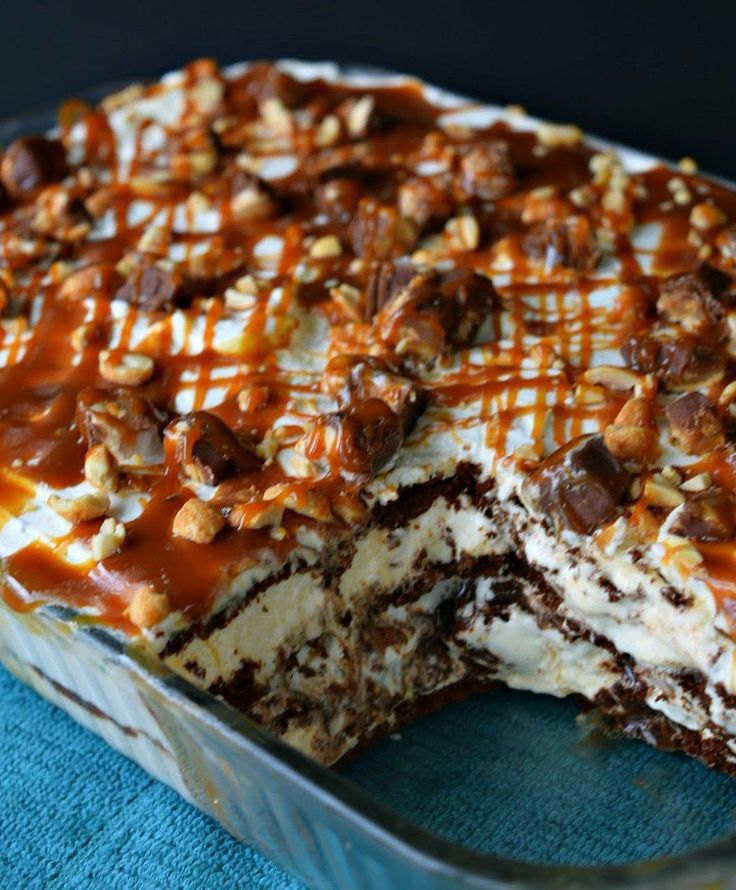 Layers of vanilla ice cream sandwiches with hot fudge, homemade whipped cream, snickers bars, and drizzled with caramel topping makes this snickers ice cream sandwich cake one sweet summer treat!