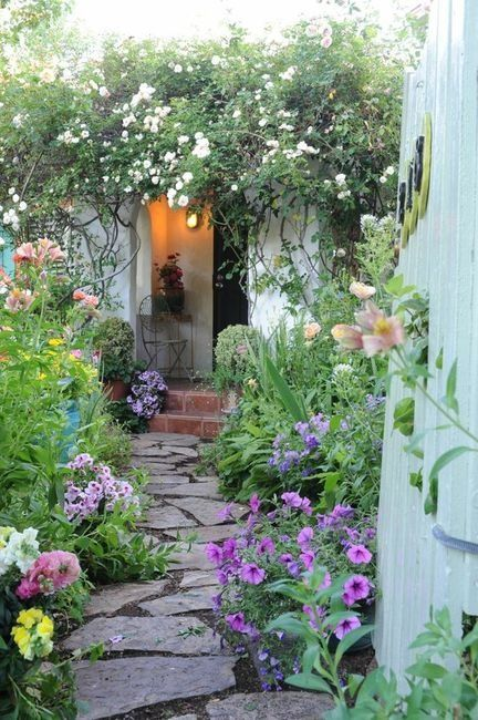 """Excellent cottage garden path: """"I love the way the plants and flowers spill over the path. It just makes it feel so exuberant. The rambling rose also makes for a lovely entry into the home. This gives me the thought of perhaps growing a rambler around the front of my garage. I have a bed nearby where I could start it and then train it up and over."""""""