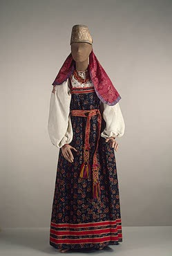 Woman's Costume   Arkhangelsk Province   Russia. Second half of 19th century  Printed linen, red calico, silk ribbon, coloured thread, galloon and amber; sewing, printed pattern and cutting. L.: sarafan 134,sash 272,shirt 38,necklace 26 cm   Source of Entry:  Expedition (1965); State Museum of Ethnography of the Peoples of the USSR, Leningrad. 1941