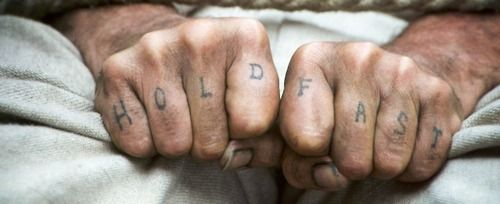 """hold fast - The word """"hold"""" spelled out on the knuckles of one hand and """"fast"""" spelled out on the other – These words are said to make it possible for the seaman to better hold onto his riggings."""