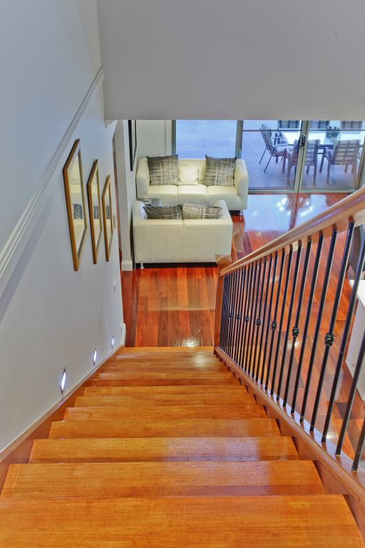 The Range - Custom Designed by Busby Homes. Polished hardwood stairs with wrought iron balustrading and timber posts.